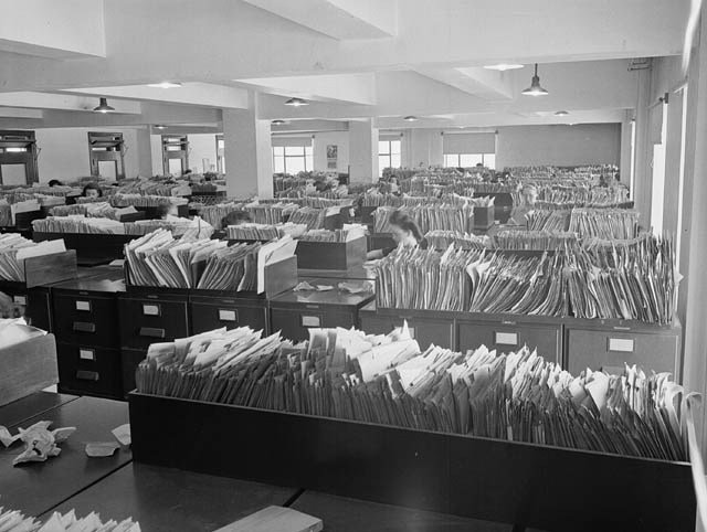 Wartime found Government employees working in poorly-lit, crowded offices such as the Records and Files Department of the Experimental Farm.  Courtesy of Library and Archives Canada. MIKAN no. 3202901.